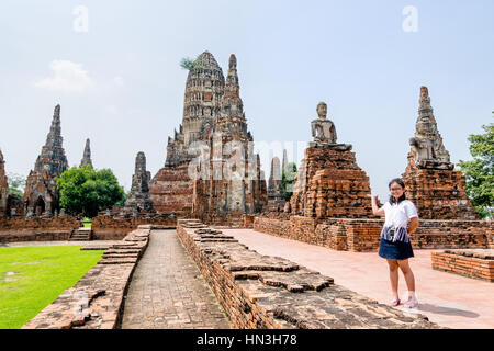 Tourist teenage girl show hand inviting to visit Wat Chaiwatthanaram is buddhist ancient temple, famous and major - Stock Image