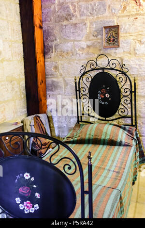 Traditional bedroom with Roman Catholic pictures and crucifixes in a Maltese house. - Stock Image