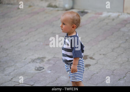 Baby Boy Walking Alone In The Street In The Old Town Of Castellar On The French Riviera, France, Europe - Stock Image