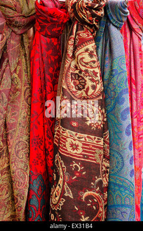 Celection of colorful head Scarves for sale on a rack at a market stall - Stock Image