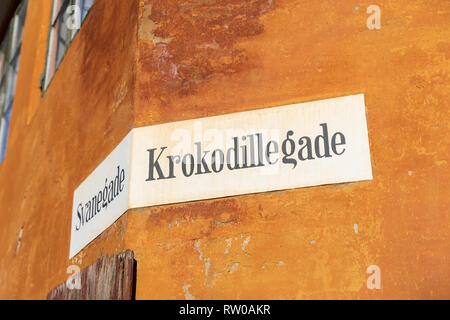 Krokodillegade ('Crocodile Street'), painted street sign on yellow wall, Nyboder, Copenhagen, Denmark - Stock Image
