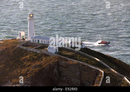 The Wales Coastal Path in North Wales. Picturesque view of South Stack Lighthouse overlooking the Irish Sea on Holy - Stock Image