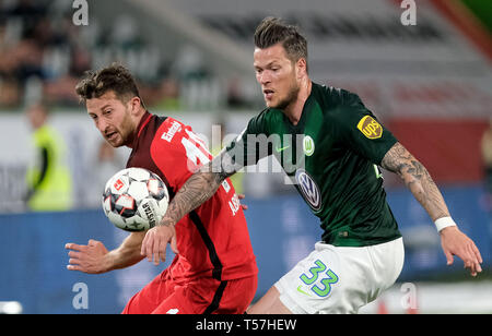 Wolfsburg, Germany. 22nd Apr, 2019. Soccer: Bundesliga, 30th matchday: VfL Wolfsburg - Eintracht Frankfurt in the Volkswagen Arena. Wolfsburg's Daniel Ginczek (r) and Frankfurt's David Abraham fight for the ball. Credit: Peter Steffen/dpa - IMPORTANT NOTE: In accordance with the requirements of the DFL Deutsche Fußball Liga or the DFB Deutscher Fußball-Bund, it is prohibited to use or have used photographs taken in the stadium and/or the match in the form of sequence images and/or video-like photo sequences./dpa/Alamy Live News - Stock Image
