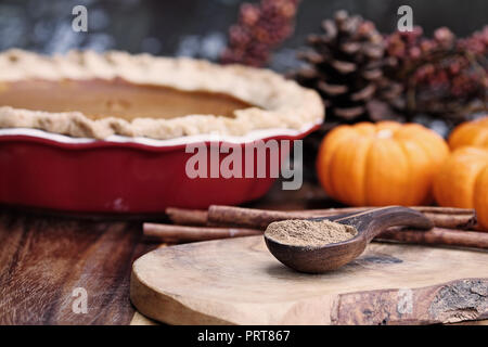 Pumpkin pie spice measured in a wooden spoon over a rustic wooden background. Pie and pumpkins in the background. Extreme shallow depth of field with  - Stock Image