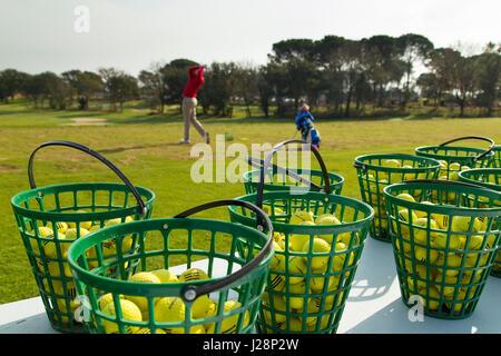 Golfers on practice range at dawn - Stock Image