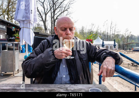 Berlin,Pankow. Weissensee Strandbad, Senior man drinks a glass of white wine at cafe at White Lake bathing beach - Stock Image