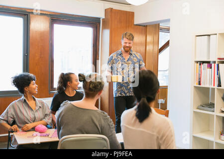Creative businessman serving coffee and tea to colleagues - Stock Image
