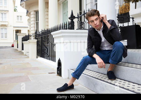 Young man sitting on steps outside house looking down street - Stock Image