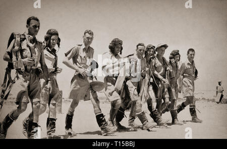 Bomber crews in hot weather outfits walking out to their aircraft prior to a raid over the African desert. The North African Campaign of the Second World War took place from June 1940 to May 1943 and included campaigns fought in the Libyan and Egyptian deserts (Western Desert Campaign, also known as the Desert War) and in Morocco and Algeria (Operation Torch), as well as Tunisia (Tunisia Campaign). - Stock Image