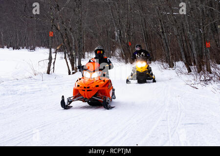 snowmobiles riding on a groomed trail along the Sacandaga River Valley near Speculator, NY USA - Stock Image