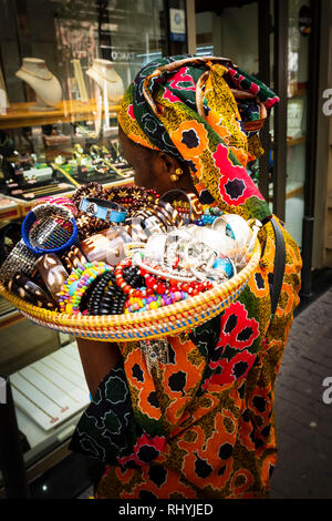 Black woman street seller in traditional dress with basket of trinkets on her shoulder Valencia Spain - Stock Image