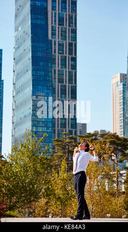 Businessman standing and stretching at park during daytime - Stock Image
