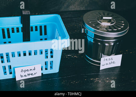 ecology and consumerism concept: spend better for less waste shopping basket next to gargabe bin - Stock Image