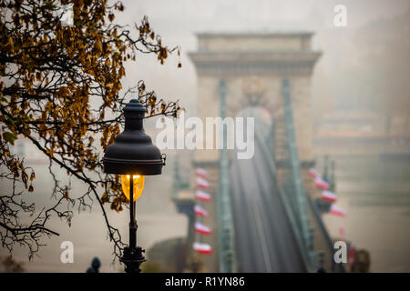 Budapest, Hungary - Street-lamp with autumn foliage and famous Szechenyi Chain Bridge at background on a foggy autumn morning - Stock Image