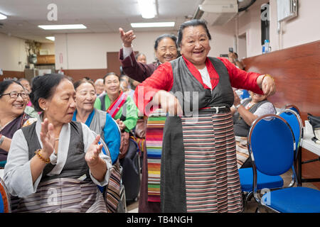 Asian women, from Nepal & Tibet, dance in the aisles at a concert of Himalayan music at the Sherpa Buddhist temple in Queens , New York City. - Stock Image