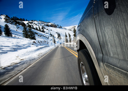 Perspective shot of SUV driving down road in snowy Colorado during winter - Stock Image