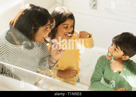 Mother and children brushing teeth in bathroom - Stock Image
