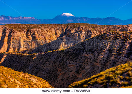 Badlands, with snowcapped La Sagra peak in background, near Galera, Granada Province, Andalusia, Spain. - Stock Image