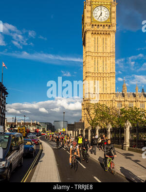 London, England - May 24, 2016: Cyclists pass the Big Ben clock tower of the Houses of Parliament on the nearly opened East-West Cycle Superhighway. - Stock Image