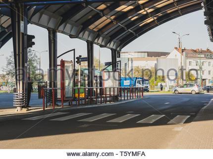 Poznan, Poland - April 18, 2019: Zebra crossing under a roof by a platform of the Rataje public transport bus station on a sunny day. - Stock Image