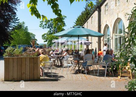 Eggleston Hall café and tea room with customers enjoying spring sunshine at the tables outside at Eggleston Durham England UK - Stock Image