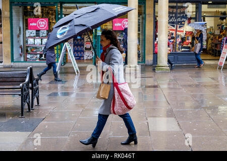Bath, UK. 8th February, 2019. As storm Eric brings gales and heavy rain across the UK a pedestrian shopping in the centre of Bath is pictured carrying an umbrella as she braves the heavy rain and wind. Credit: Lynchpics/Alamy Live News - Stock Image