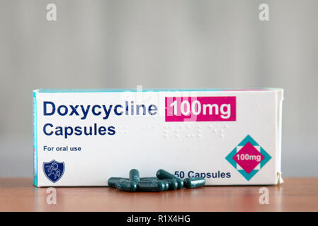 Stock photo of a box of Doxycyline, an antibiotic used against several infactions, and as anti-malarials, with some capsules loose on the table below. - Stock Image