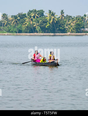 Vertical view of ladies paddling across a lagoon in a canoe in Alleppy, India - Stock Image