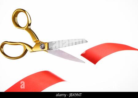 Golden scissors cutting red ribbon/ tape - Stock Image
