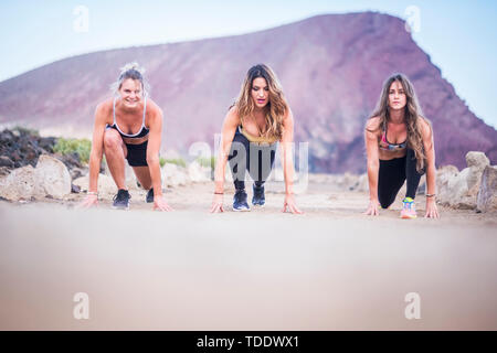three beautiful runner girls young ready to start and run for hard workout and fitness outdoor activity. build your new and strong body near the beach - Stock Image