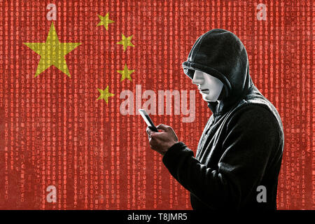 Chinese hooded hacker with mask holding smartphone - Stock Image