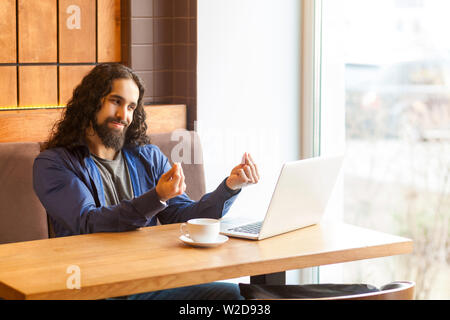 Portrait of handsome young adult man freelancer in casual style sitting in cafe and agrees with his employer for payment through webcam and showing ca - Stock Image