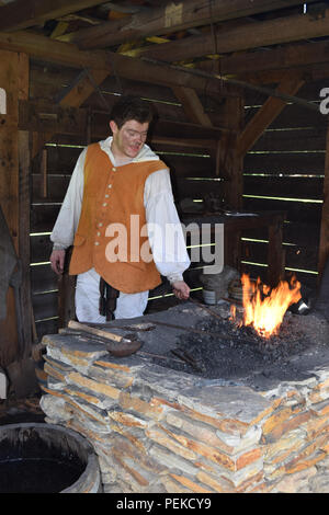 A demonstration of a Colonial Blacksmith working Iron. - Stock Image