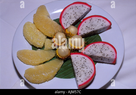 Tropical fruits served on a dish in Vietnam South East Asia dragon fruit Hylocereus undatus pomelo and rambutan - Stock Image