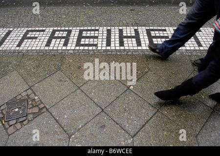 pavement sidewalk checkpoint charlie berlin germany deutschland travel tourism tiles  freiheit pedestrians passers - Stock Image