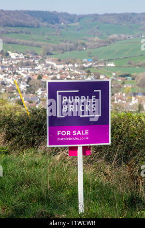Purple Bricks house for sale sign in open countryside above the village of Sidford, nr Sidmouth, Devon, UK - Stock Image