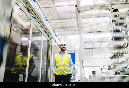 A portrait of a happy industrial man engineer in a factory, hands in pockets. Copy space. - Stock Image
