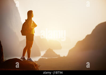 Beautiful woman with backpack at sunrise or sunset on mountain top - Stock Image