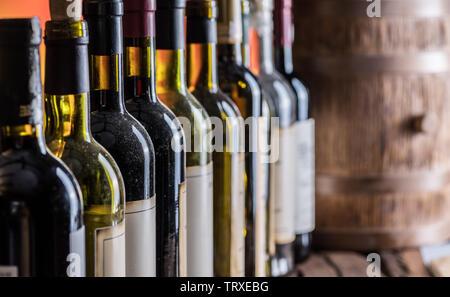Wine bottles in row and oak wine keg. - Stock Image