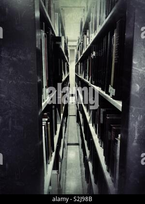 Narrow gap between two moving book shelves in a library - Stock Image