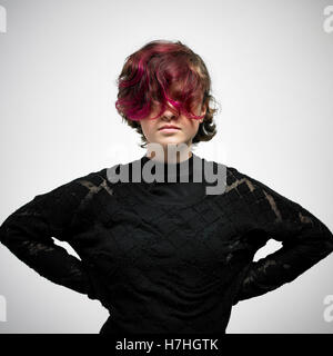 studio portrait of girl teen with long bangs hands on hips - Stock Image
