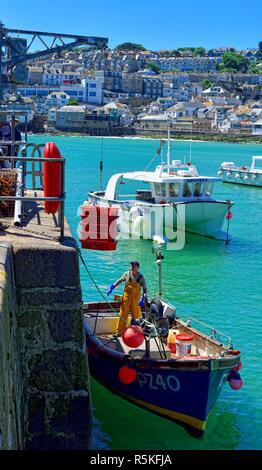 Small fishing boat being loaded with red crates full of fishing bait,St Ives,harbour,England,UK - Stock Image