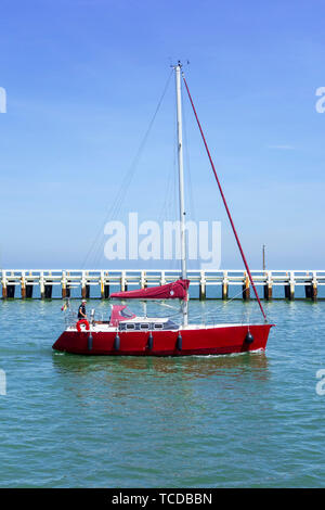 Red sailboat / yacht sailing past the wooden jetty at Nieuport / Nieuwpoort, seaside resort along the North Sea coast, West Flanders, Belgium - Stock Image