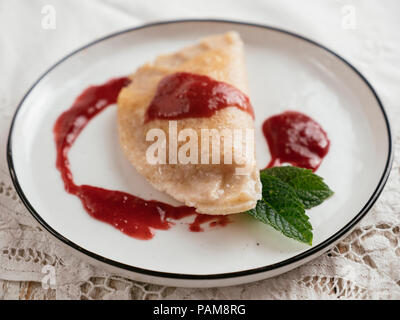 Home made perogi with a vegan cottage cheese filling and a plum sauce. - Stock Image