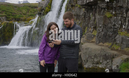 Boyfriend and girlfriend using cell phone near waterfall over remote rock cliffs - Stock Image