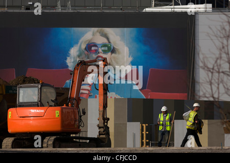 An excavator and aspirational poster on wall during building of 2012 Olympic Westfield City shopping centre, Stratford. - Stock Image