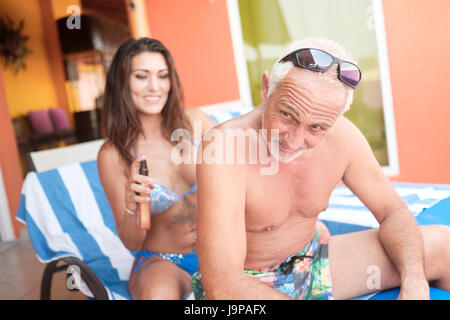 Young woman spraying sunscreen lotion on older man's back while both sit on lounge chair - Stock Image