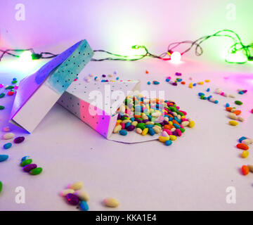 Christmas decoration triangle git boxes with colorful candies spread as confetti under party lights for celebration - Stock Image