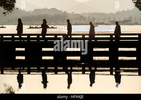 Five tourists in silhouette cross a bridge at Hangzhou's West Lake scenic area - Stock Image