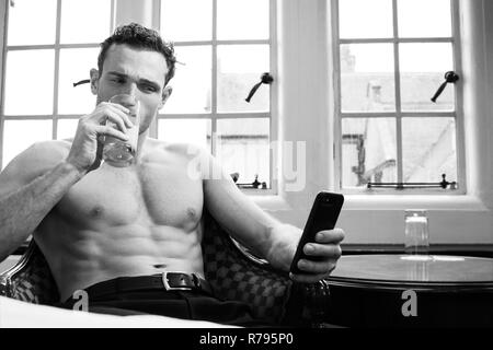 Good looking man with muscular pecs and six pack abs drinking juice while using mobile phone next to window - Stock Image